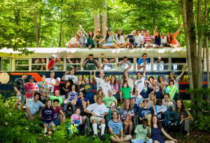80 people with and without disabilities smiling, waving, hugging, surrounding each other and the Zeno bus in the woods, on a bright summer day.